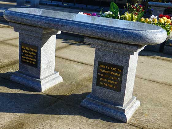 A Memorial Bench featuring two black granite plaques with inscriptions